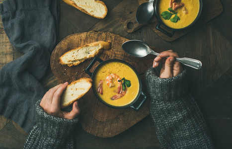 Woman in sweater eating corn soup with prawns top view