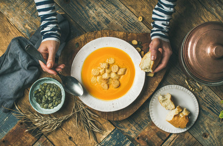 Fall warming pumpkin cream soup with seeds and bread