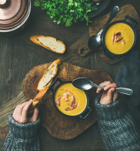 Woman in sweater eating corn creamy soup with shrimps