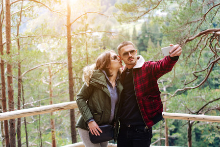 man and woman in the forest take selfie