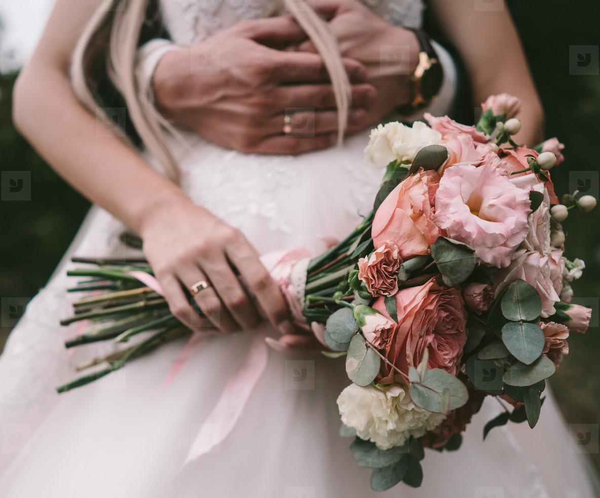 The bridegroom embraces the brides waist