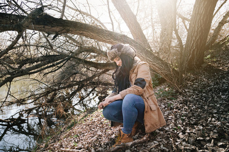 Young attractive woman wearing russian leather bomber hat next to the river