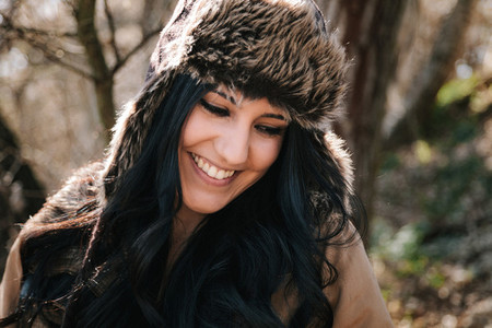 Young attractive woman smiling wearing russian leather bomber hat