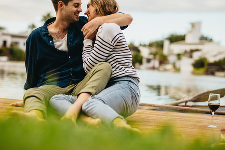 Couple sitting outdoors near a lake in a romantic mood
