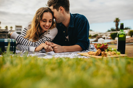 Romantic couple out on picnic lying on the ground