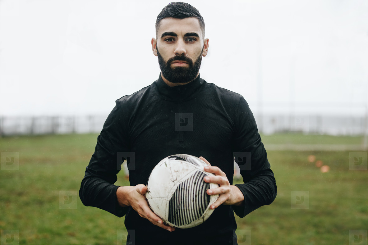 Portrait of a soccer player standing on field holding a ball