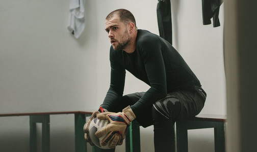 Footballer sitting in dressing room holding a football