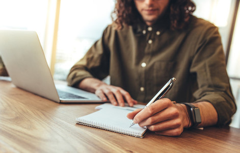Businessman writing notes in a notepad