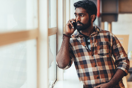 Man talking over mobile phone standing beside a window