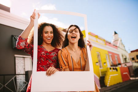 Excited women outdoors with a photo frame