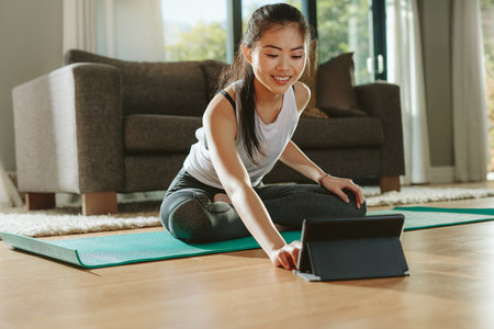 Fitness woman watching training videos on digital tablet