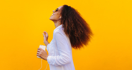 African girl having fun listening music on smartphone