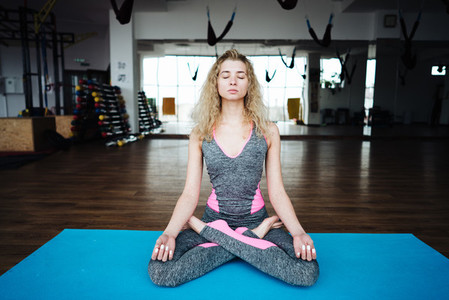 Young slim blond woman in yoga class