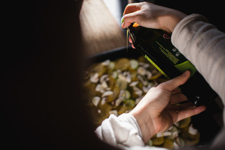 Pouring olive oil over vegetable