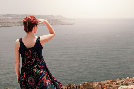 Young redhead woman with a topknot looking far away the sea with her hand over head from a cliff with her long dress moving with wind