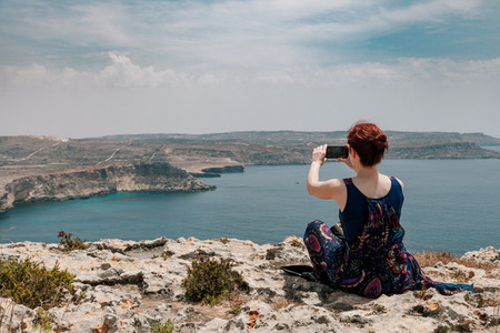 Young redhead woman with a topknot taken a picture with her phone from a cliff with views of bay