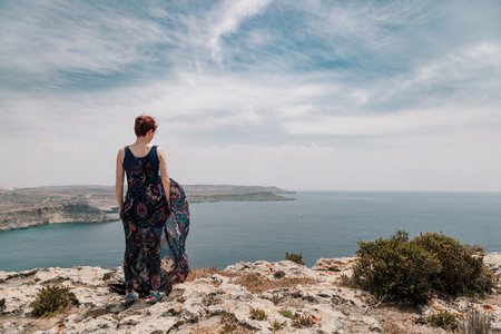Young redhead woman from the edge of cliff wearing a long dress moving with the wind