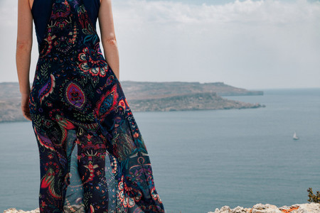 Close up young woman from a cliff wearing a long dress moving with the wind