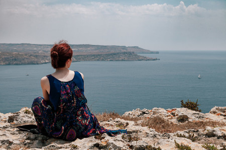 Young redhead woman with a topknot sitting on the edge of a cliff looking far away the sea