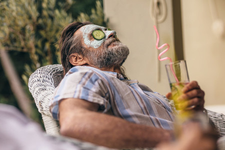 Retired man relaxing with clay mask on face