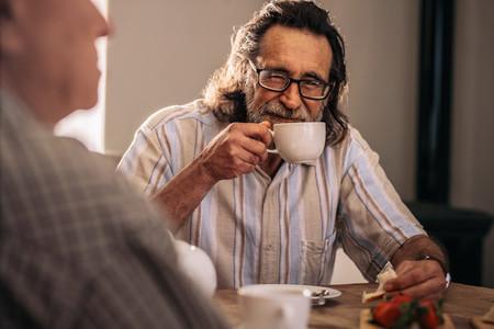 Retired man sitting with friend having tea