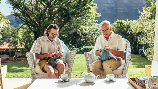 Two old men knitting in patio