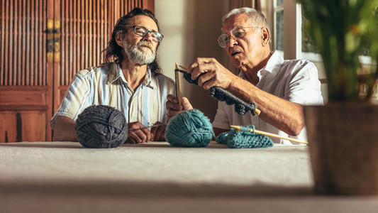 Senior man teaching his friends the art of knitting