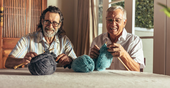 Retired men doing pastime at home knitting