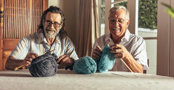Retired men doing pastime at home knitting