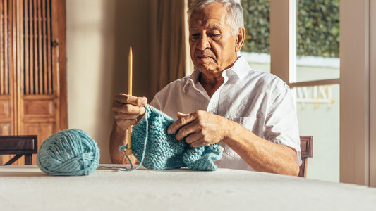 Retired senior man knitting warm clothes