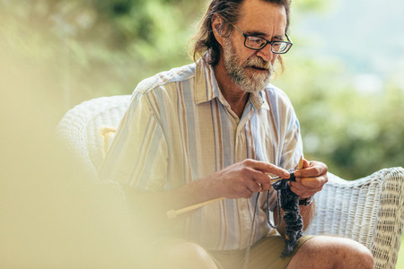 Elderly man with beard knitting