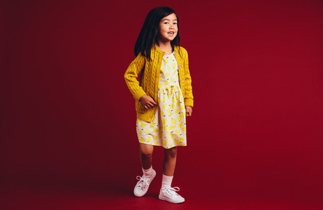 Little girl standing against a red background