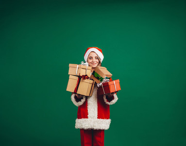 Smiling girl in santa claus dress holding her christmas gifts