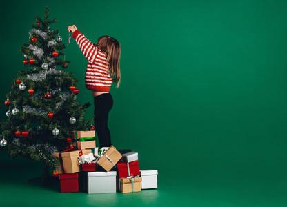 Kid decorating a christmas tree