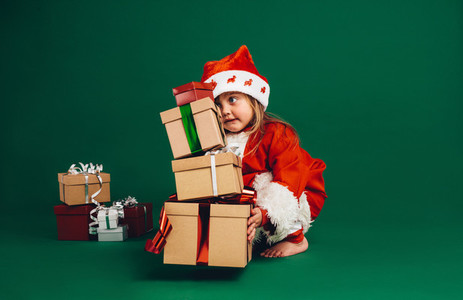 Kid dressed as santa lifting gift boxes
