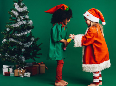 Kids in christmas costumes playing with a toy