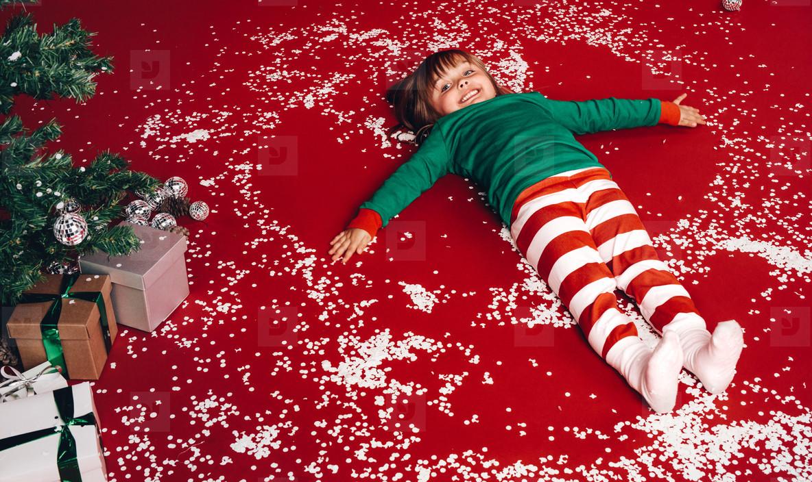 Kid lying down on floor beside a christmas tree