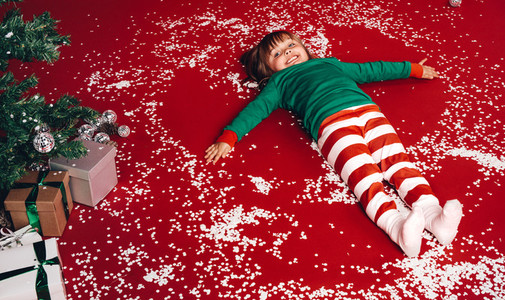 Kid lying down on floor beside a christmas tree