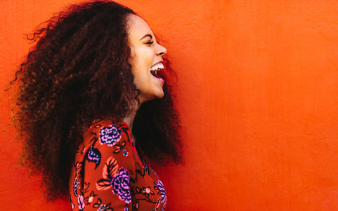 Laughing african young woman with curly hair