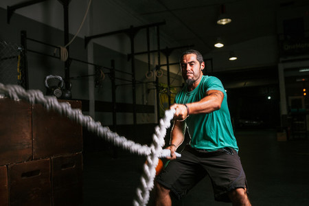 Athletic young man doing some cross fit exercises with a rope indoor