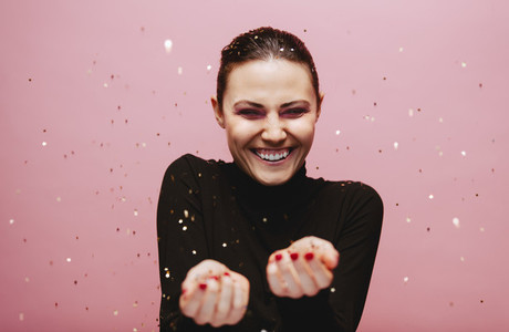 Beautiful young woman smiling with confetti