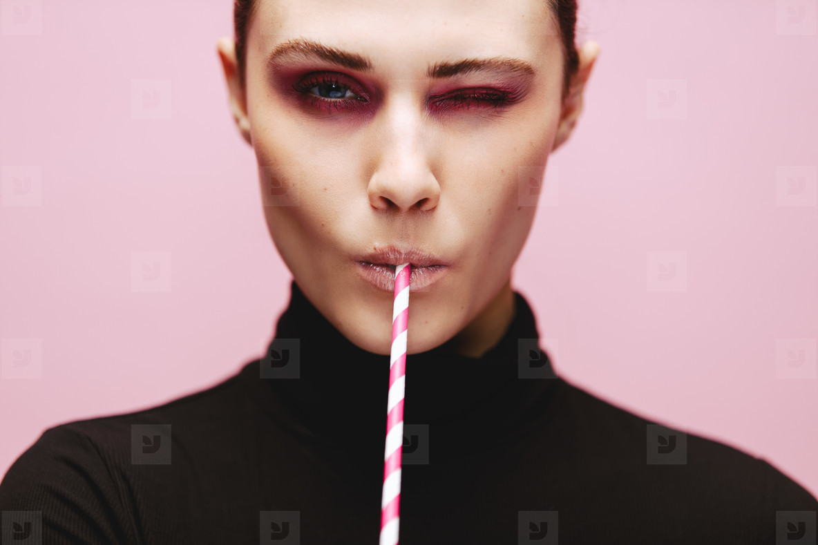 Beautiful woman winking with a straw