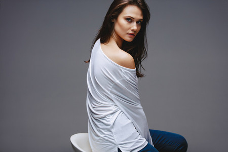 Beautiful woman in casuals sitting on stool