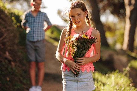 Girl standing in park holding a bunch of flowers