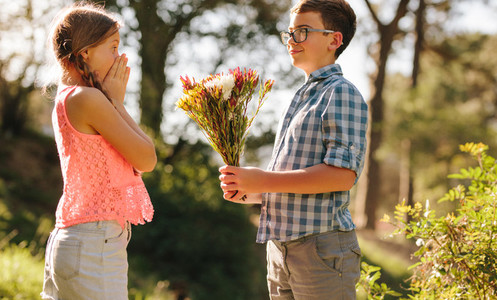 Boy proposing to his girlfriend with flowers
