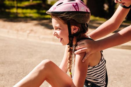 Happy girl sitting on street wearing a bicycle helmet