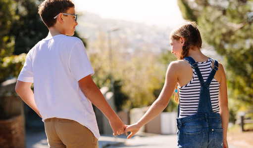 Happy kids in love standing on street and talking