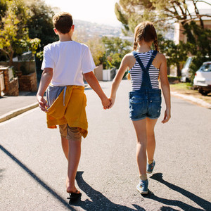 Kids in love walking on street holding their hands