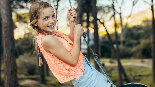 Smiling girl playing on a tire swing in a park