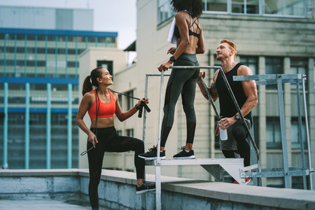 Fitness people relaxing after workout standing on rooftop